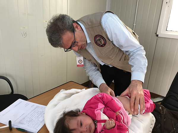 Tarif Bakdash, an MEHP candidate, examines a child with an abnormal spine in a refugee camp in Amman, Jordan, where the population is 35,000. On the home page, Bakdash surrounded by Syrian refugee children.