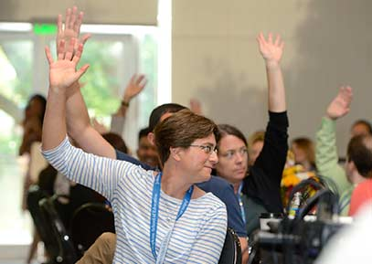 People raising one hand at a conference