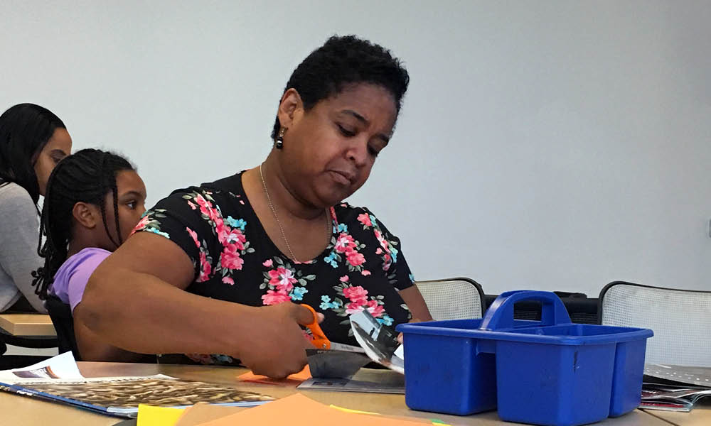 Woman cutting pieces out of magazine