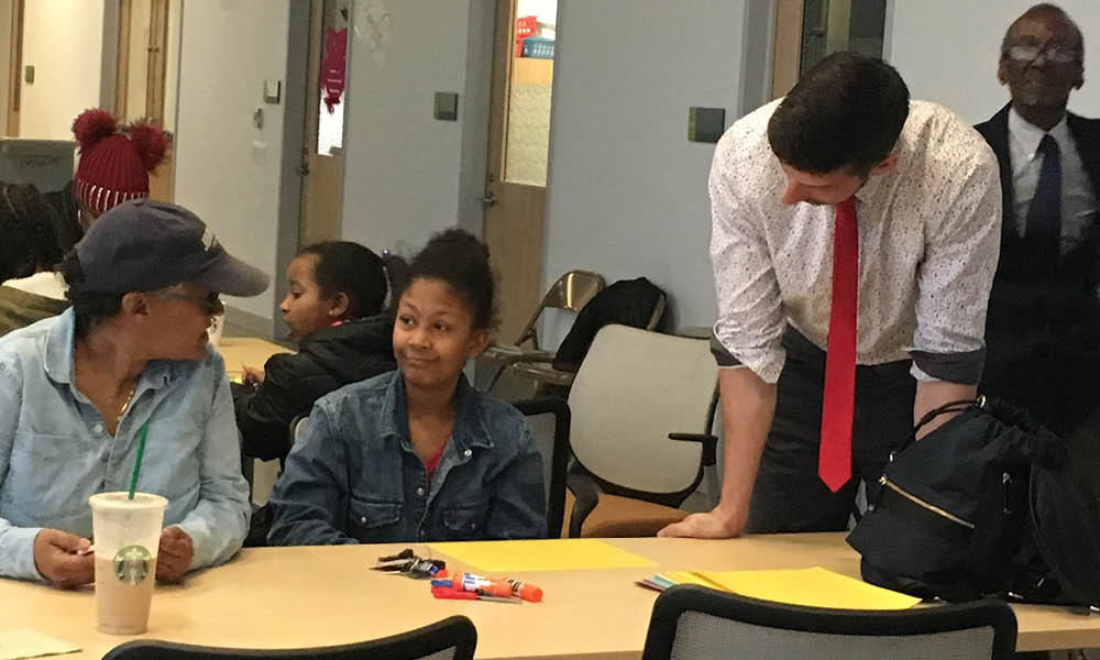 Henderson-Hopkins student, her guardian, and teacher talking around table