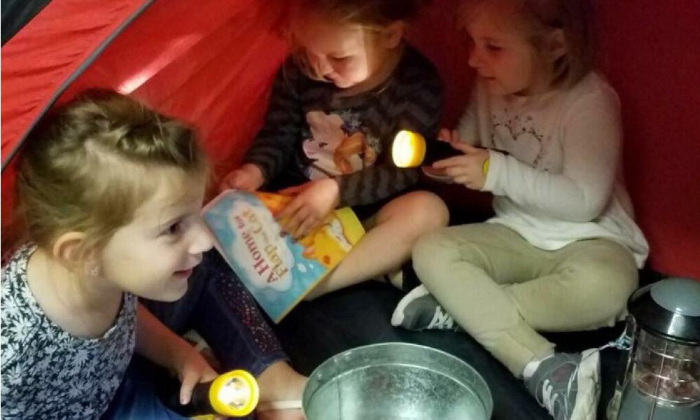 Three children in tent with flashlights