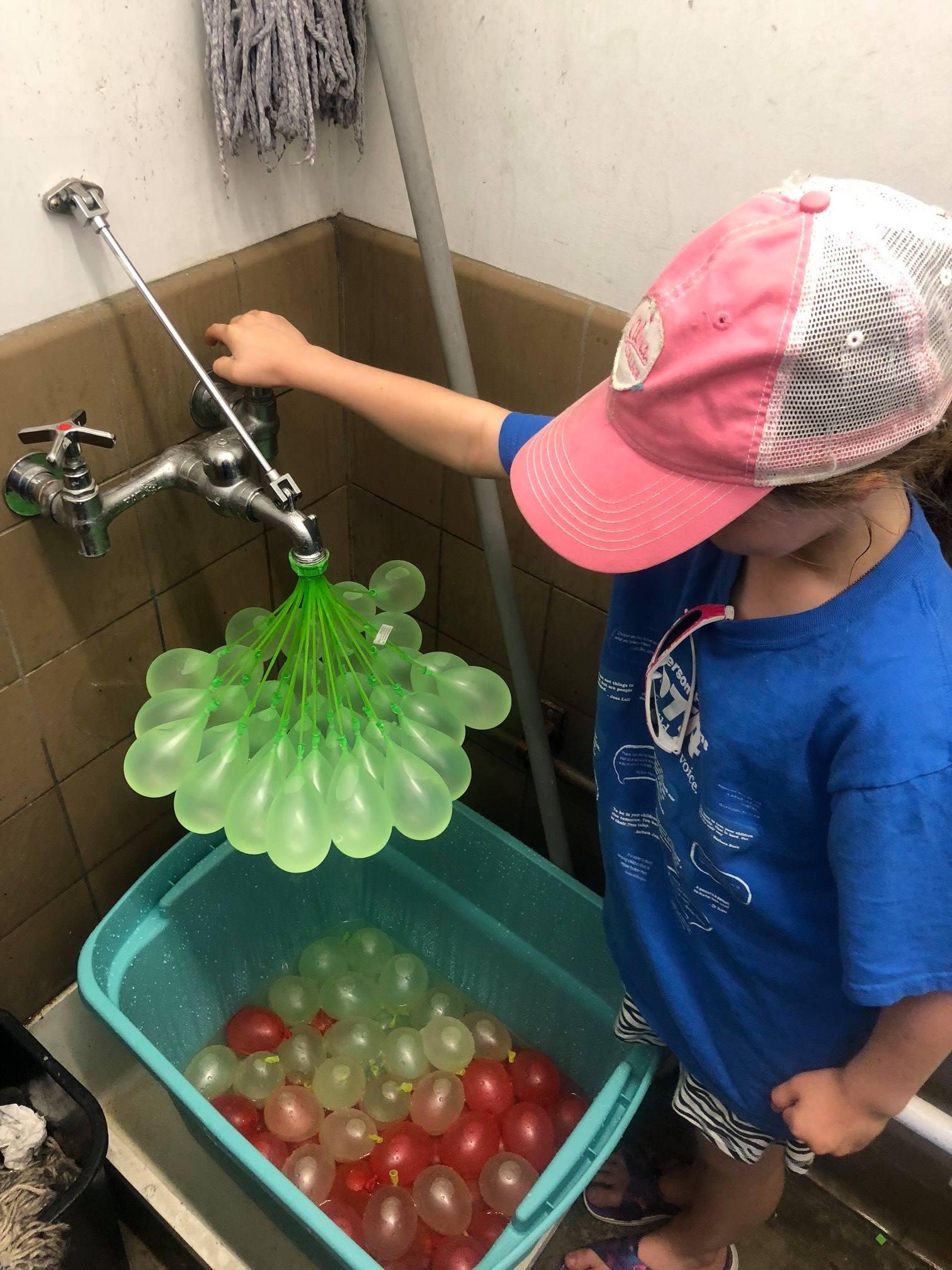 Girl filling water balloons
