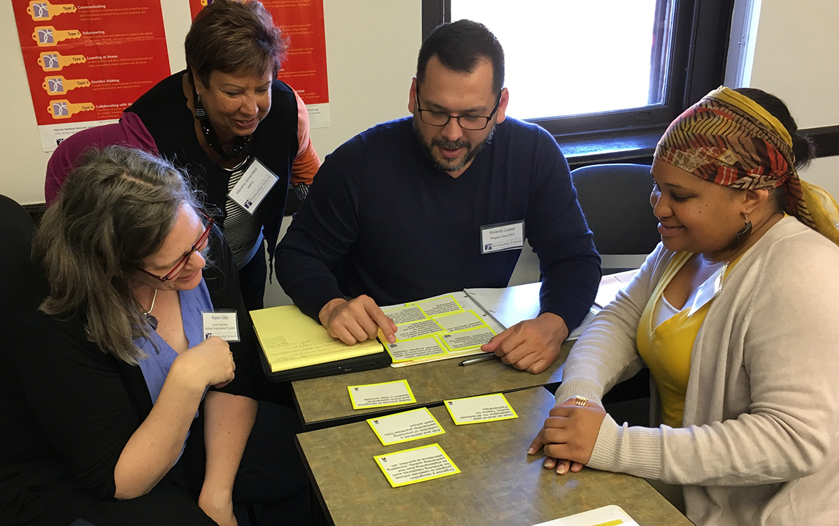 Four NNPS trainees discuss around a table