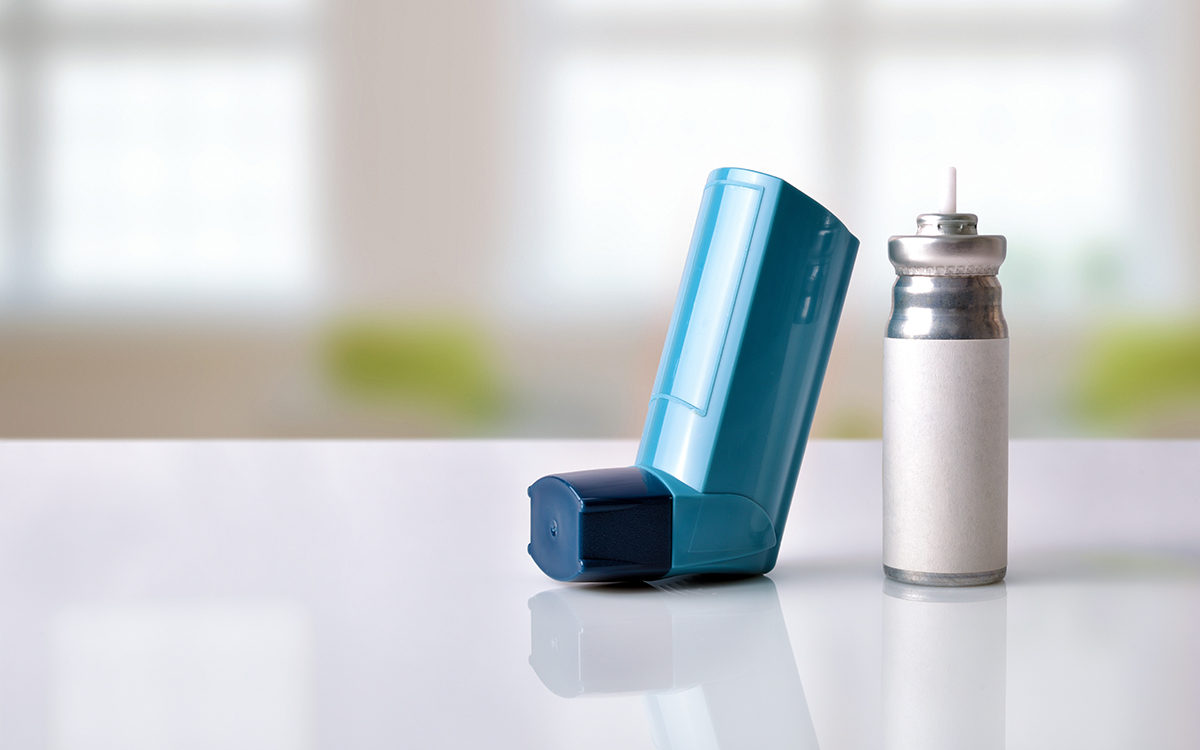 Cartridge and blue medicine inhaler on white glass table in a room. Front view Horizontal composition