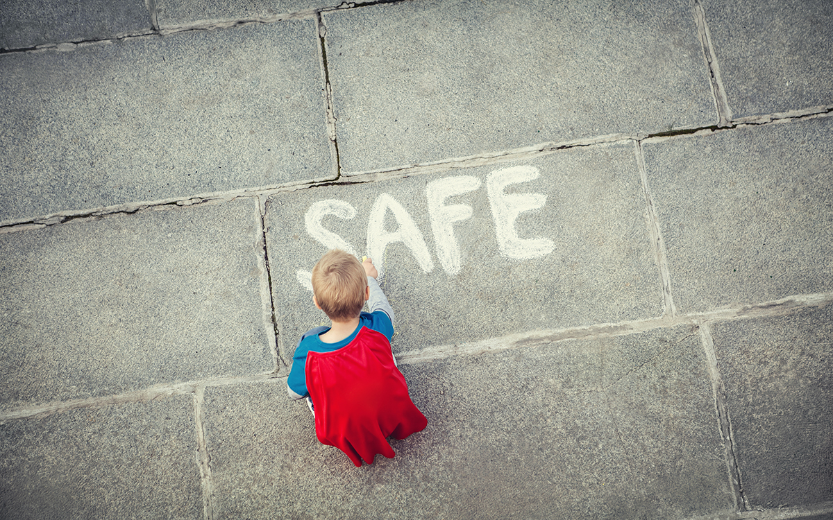 Little boy draws safe inscription outdoors