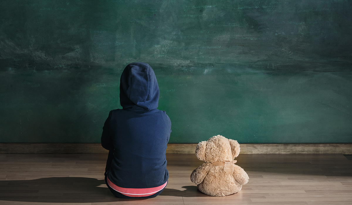 Little girl with teddy bear sitting on floor in empty room.