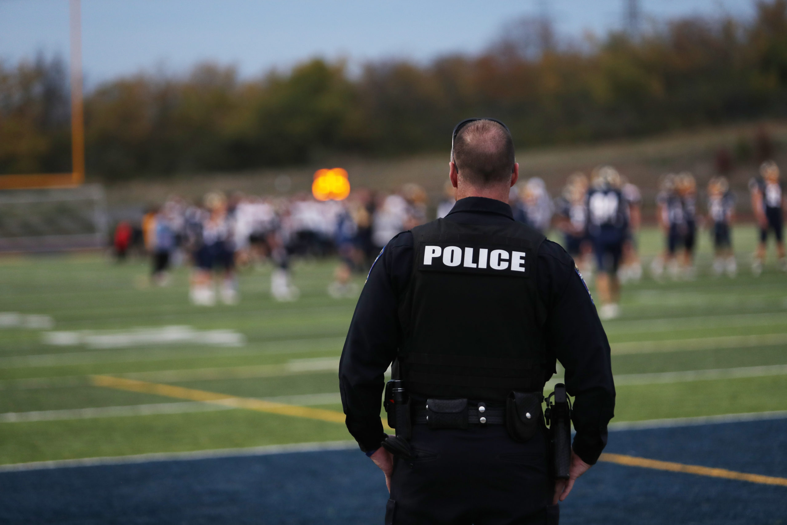 A local police officer works during a high school football game.