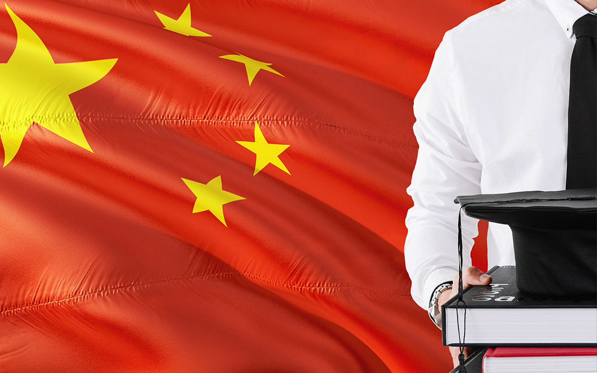 A person holding books and graduation cap over China flag background.