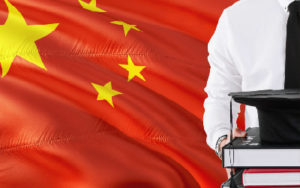 Student with books stands in front of the Chinese Flag
