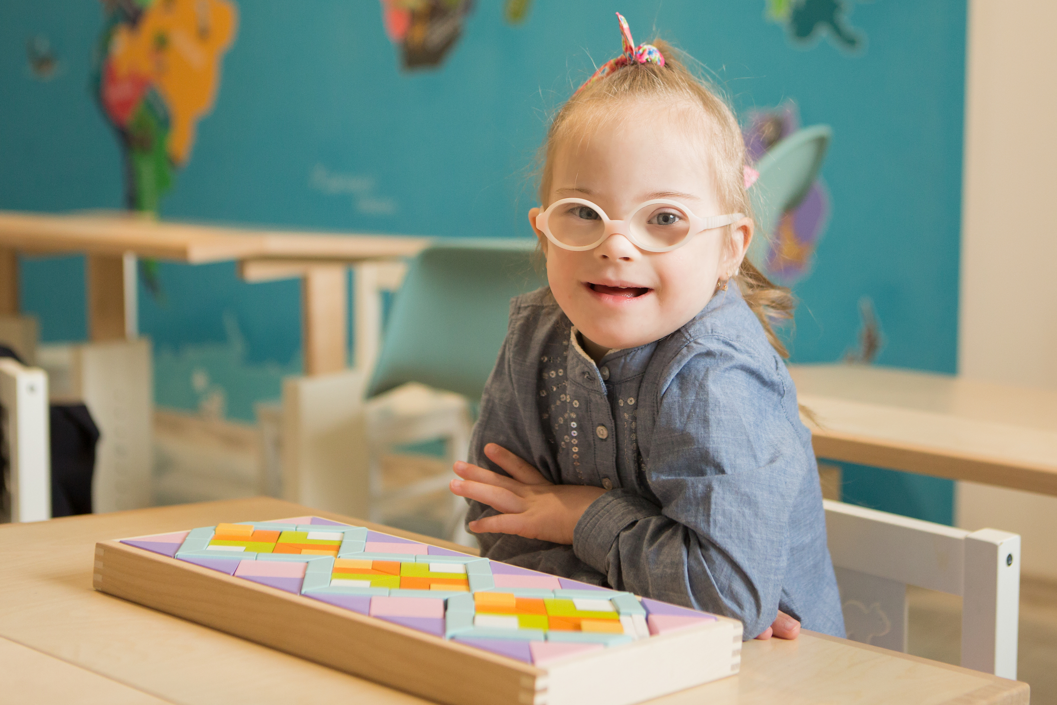 A child with Down syndrome in a classroom looking at the camera