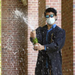Graduate wearing mask with champagne