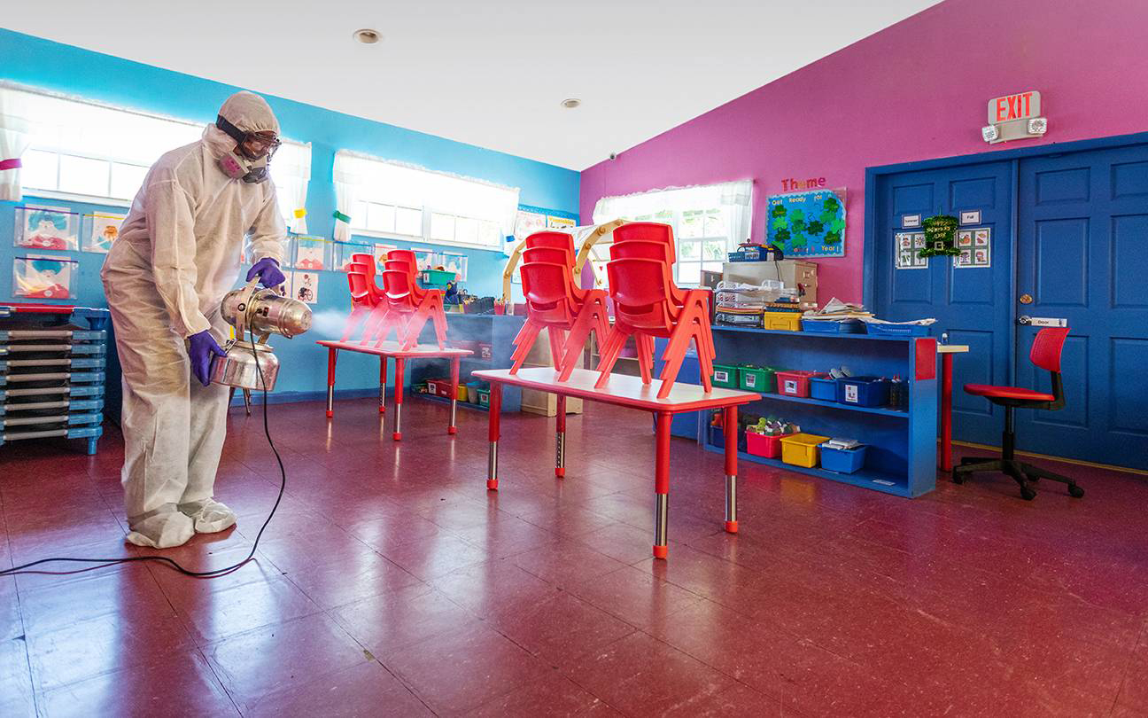 Person disinfecting elementary school room