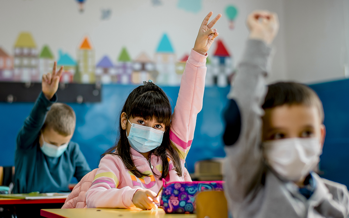 Elementary school children wearing a protective face masks in the classroom