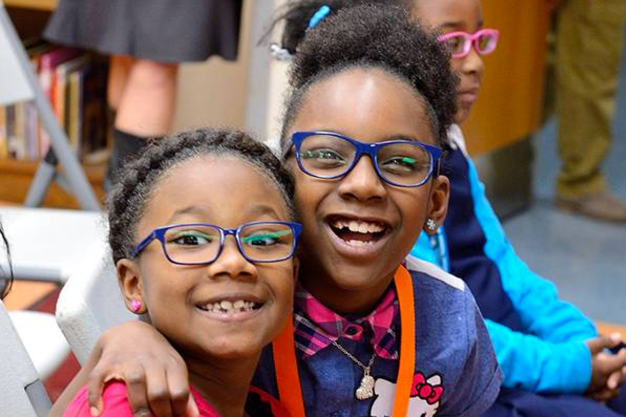 Two children smiling wearing glasses
